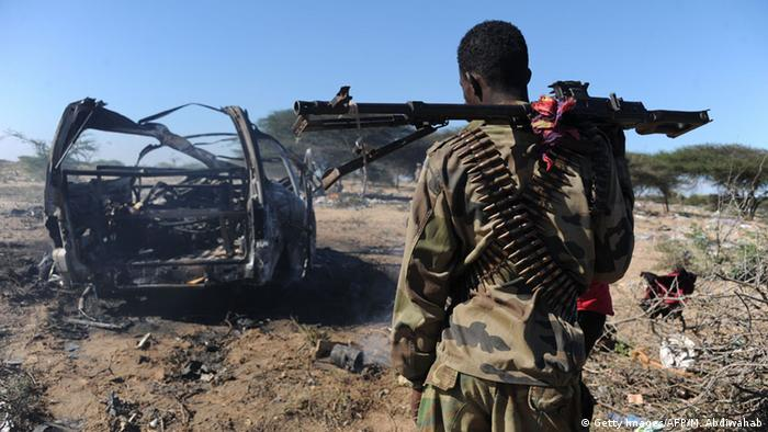 A soldier looks at the burnt out wreckage of a car, following an al-Shabab suicide bombing