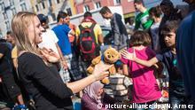 1. Sept 2015 Eine Mitarbeiterin der Bürgerinitiative Flüchtlingshilfe München verteilt am 01.09.2015 am Hauptbahnhof von München (Bayern) Stofftiere an Flüchtlingskinder. Foto: Nicolas Armer/dpa +++(c) dpa - Bildfunk+++