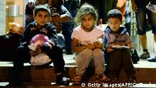 31.08.2015+++ Young children sit on the steps of the main train station in Munich, southern Germany, after migrants arrived from Hungary on August 31, 2015. Hungarian police had been stopping refugees and migrants from boarding international trains since mid-August, even if they had bought valid tickets, but on August 31 the police were, suddenly, nowhere to be seen. AFP PHOTO / CHRISTOF STACHE (Photo credit should read CHRISTOF STACHE/AFP/Getty Images)