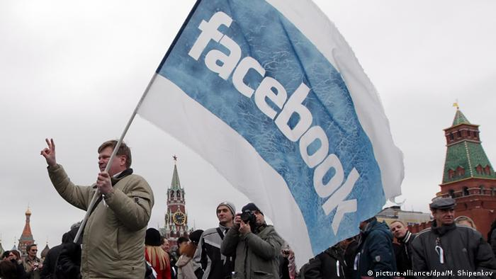 A man holds a Facebook flag at protests in Moscow (photo: EPA/MAXIM SHIPENKOV)