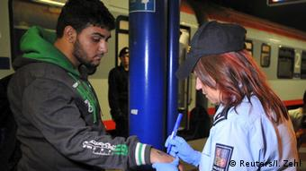 A Czech police officer writes a number on the skin of a refugee in Breclav