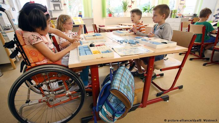 Child in a wheelchair sitting at schooldesk with other kids (picture-alliance/dpa/B. Wüstneck)