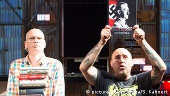 Zwei Schauspieler auf der Bühne, einer hält Mein Kampf wie eine Trophäe in die Luft (Foto: picture alliance/dpa/S. Kahnert)