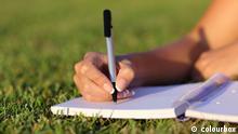 Symbolbild Frauenhand Schreiben Wiese