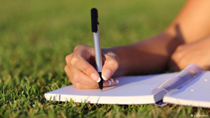 Symbolbild Frauenhand Schreiben Wiese (colourbox)