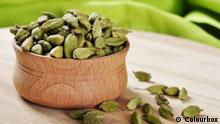 Green Cardamom Pods in wooden bowl on cutting board