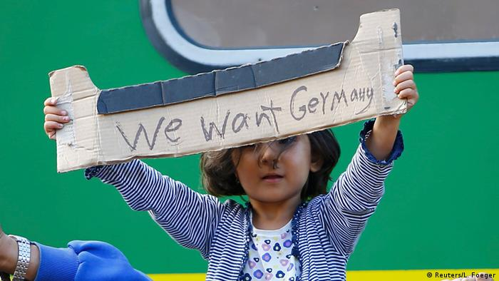 Refugee girl standing next to a green train and holding up a sign saying We want Germany