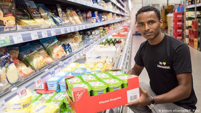 An Eritrean refugee interning at a German supermarket