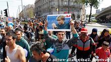 Ungarn Flüchtlinge in Budapest machen sich zu Fuß auf nach Deutschand sie tragen Plakate von Angela Merkel