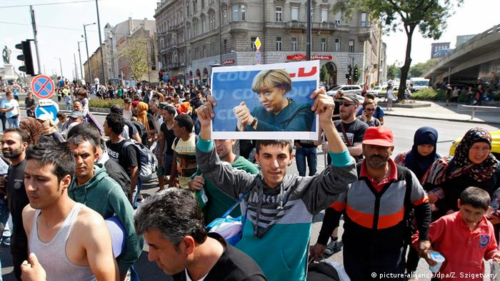 Refugee walking to Austria carrying a photo of Angela Merkel