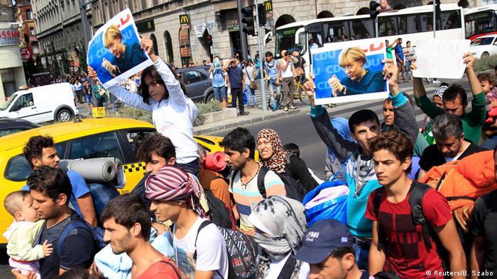 Refugees in Budapest holding posters of Angela Merkel