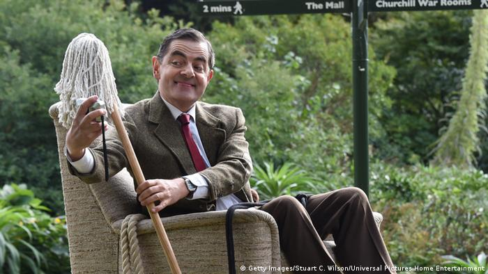 Mr Bean holding a mop