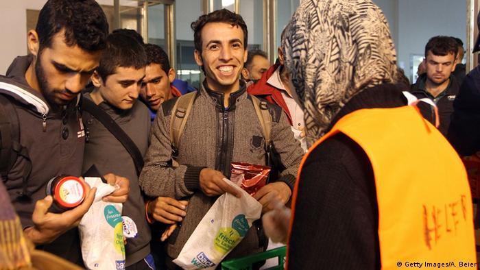Беженцы получают продукты питания от волонтера