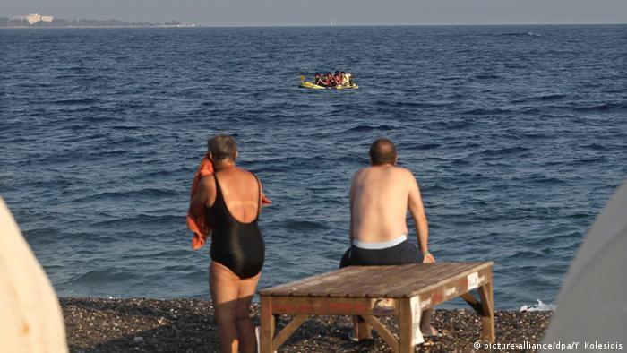 Остров Кос (Греция). Отдыхающие смотрят на лодку с пакистанскими беженцами.