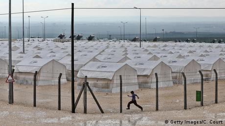 Urlauber der Insel Kos laufen an Zelten von Flüchtlingen vorbei