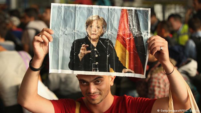 Беженец с плакатом, на котором изображена Ангела Меркель