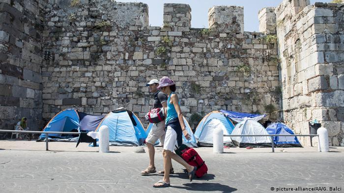 Туристы идут мимо палаток беженцев.