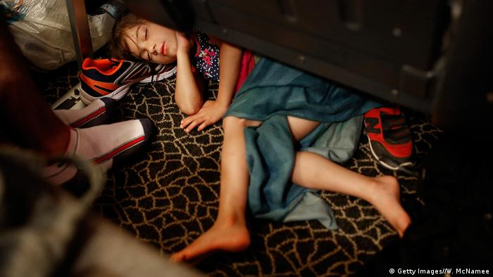Syrian refugee girl sleeping under a seat on a ferry