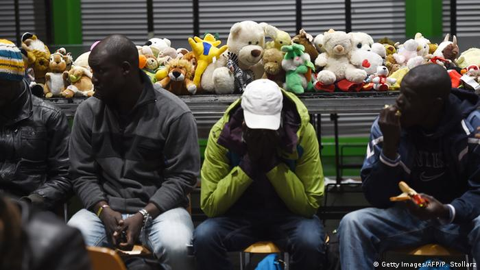 Refugees sit in front of a row of stuffed animals at Dortmund central station. (Photo: PATRIK STOLLARZ/AFP/Getty Images)