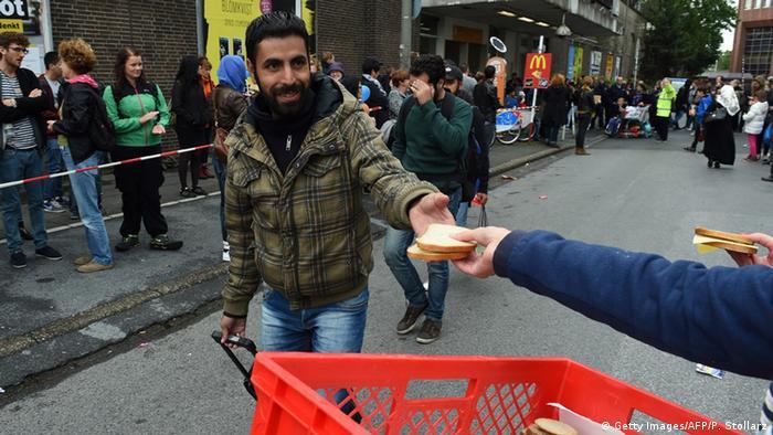 A refugee is handed food after he arrives in Dortmund