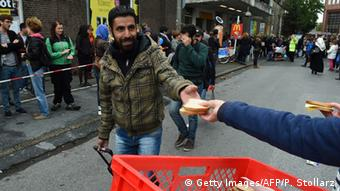 A refugee taking a sandwich from an outstretched hand. (Photo: PATRIK STOLLARZ/AFP/Getty Images)