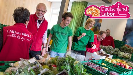 Die Moderatorin und der Moderator des Deutschlandlabors stehen mit vier weiteren Menschen an einer Lebensmittelausgabe.
