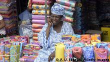 Bildunterschrift:TO GO WITH AFP STORY BY BEN SIMON A shop owner makes a call at Oshodi market in Lagos on February 25, 2015. Congested streets lined with shops selling everything from plastic sandals to instant passport photos and hawkers shouting for customers above deafening car horns: the Oshodi market offers a snapshot of life in Nigeria's largest city. Like other parts of Lagos, Oshodi has seen outbreaks of political violence in the run-up to March 28 general elections, much of it blamed on 'Area Boys' -- gangs of youths readily available for mercenary work. AFP PHOTO/PIUS UTOMI EKPEI (Photo credit should read PIUS UTOMI EKPEI/AFP/Getty Images)