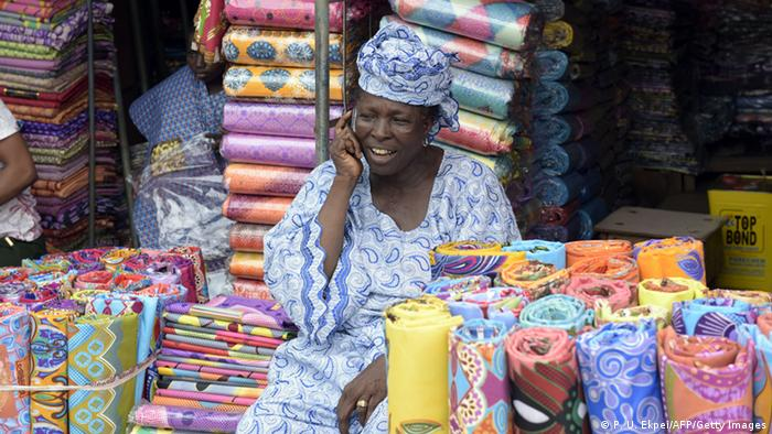A woman market seller sitting among rolls of fabric and talking on a cellphone