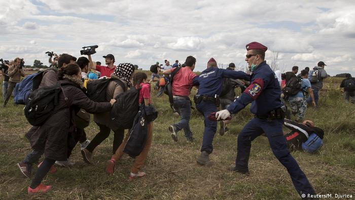 Hungarian police officers stop migrants as they try to escape on a field nearby a collection point in the village of Roszke, Hungary, September 8, 2015.