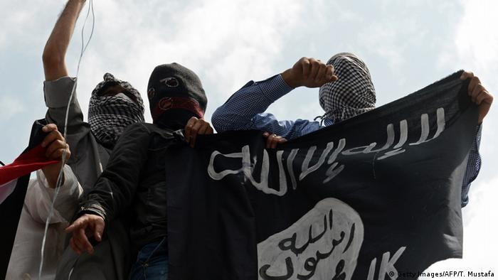 Demonstrators hold up a flag of the Islamic State of Iraq and the Levant (ISIL) during a demonstration.