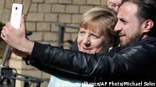 An unidentified man takes a picture of himself and German Chancellor Angela Merkel, left, during Merkel's visit at a registration center for migrants and refugees in Berlin, Germany, Thursday, Sept. 10, 2015. (AP Photo/Michael Sohn)