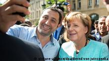 Refugee in Berlin taking selfie with Angela Merkel in 2015
