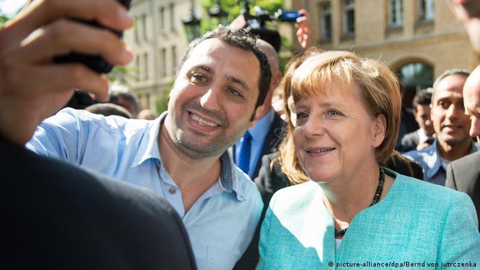 Seorang pengungsi di penampungan pengungsi di Berlin membuat swafoto dengan Kanselir Jerman Angela Merkel