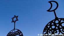 A star of david and a crescent moon decoration sit against a blue sky (picture-alliance/Godong)