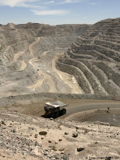 An open cut uranium mine, with a truck carrying stones along a dirt road.