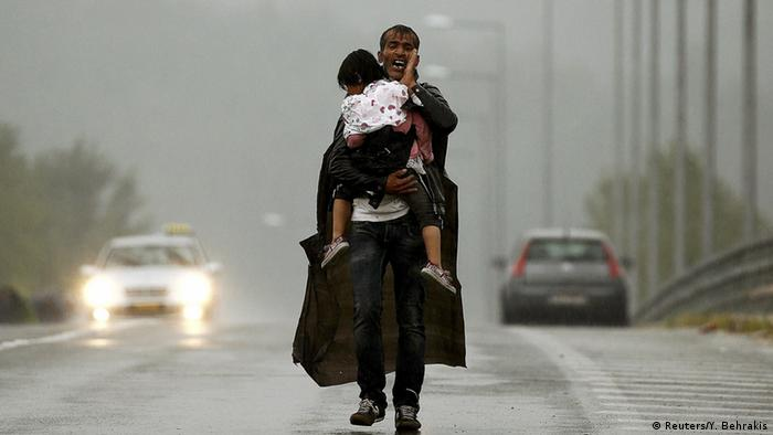 A refugee walking in the rain on a road in Macedonia while holding a child Photo: REUTERS/Yannis Behrakis