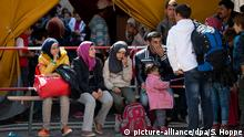 Flüchtlinge, die kurz zuvor mit Zügen angekommen sind, warten am 12.09.2015 auf dem Hauptbahnhof in München (Bayern) auf einen Bus, der sie in eine der diversen Erstaufnahmeeinrichtungen fahren soll. Foto: Sven Hoppe/dpa +++(c) dpa - Bildfunk+++