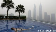 A woman swims in a rooftop pool in front of the Petronas Towers, shrouded by haze, in Kuala Lumpur, Malaysia, September 13, 2015. The so-called haze, caused by slash-and-burn clearances on the islands of Sumatra and Borneo, has pushed air quality to unhealthy levels in Malaysia and neighboring Singapore. REUTERS/Olivia Harris