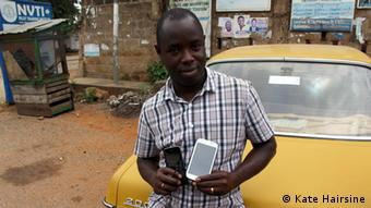 A man holds his two mobile phones in the streets of Ghana (Kate Hairsine)