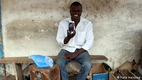 Photo from Abdulai Tanko holding a smartphone surrounded by tools and spare tyres.