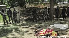 September 13, 2015 Bildunterschrift:Cameroon security forces look on while a victim of a twin suicide attack lies on the ground in the extreme north village of Kolofata on September 13, 2015. Two suicide bombers killed seven people on September 13 in attacks in the northern Cameroon town of Kolofata, near the border with Nigeria, an army official said. 'According to initial information, nine people have died and 20 were injured,' he said, giving a toll that included the bombers. Kolofata is near Kerawa where at least 20 people died in two suicide attacks on September 3. AFP PHOTO / STRINGER (Photo credit should read -/AFP/Getty Images)