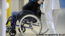 An auxiliary nurse assists a patient in a wheelchair in a geriatric unit at the CHU Angers teaching hospital in Angers, western France, on October 23, 2013. The Angers hospital employs 6,000 people including 980 doctors. AFP PHOTO / JEAN-SEBASTIEN EVRARD (Photo credit should read JEAN-SEBASTIEN EVRARD/AFP/Getty Images)