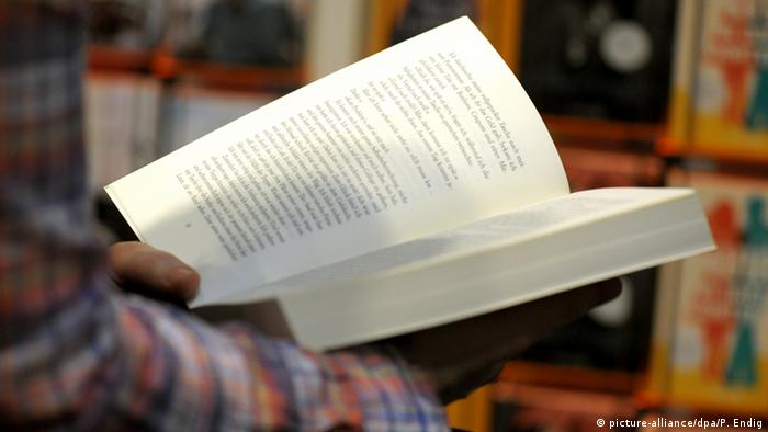 Hands of a man holding a book (picture-alliance/dpa/P. Endig)