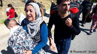 Migrants walk on a highway connecting Turkey and Greece