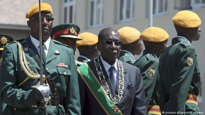 Zimbabwe President Robert Mugabe, center, inspects the guard of honor during the opening of Parliament in Harare