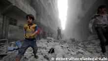 Image #: 39424332 Syrians walk on the rubble of buildings after a missile fired by Syrian government forces hit a residential area in the al-Sukari district in the northern Syrian city of Aleppo on September 15, 2015. Photo by Ameer al-Halbi APA /Landov
