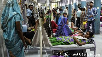 18 year-old patient Radha, suffering from dengue, shares her bed with other patients in a casualty ward of a government hospital in New Delhi (Photo: Chandan Khanna/AFP/Getty Images)