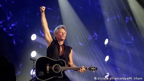Bon Jovi performing on stage with a guitar in his hand