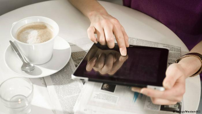 Person having a coffee whilst using a Tablet