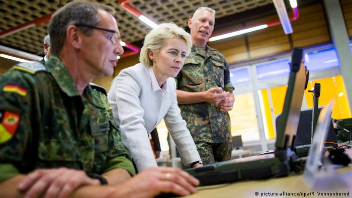 Ursula von der Leyen looking at computers with soldiers